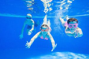 Kinder tauchen in Schwimmbecken